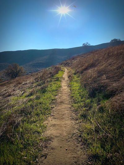 """To Close To The Sun"" A hiking trail elevates toward the sky while a distant hang glider appears to be heading directly into the bright afternoon sun. Hills Hiking Trail Trails Blue Sky Hang Gliding Sunflare Sunbeam Sun Sky Sunlight Landscape Land Nature Environment Scenics - Nature"