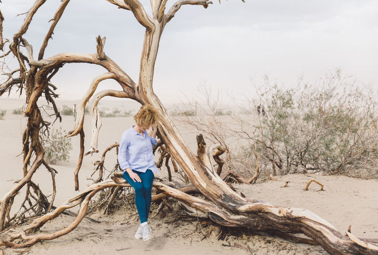 Arid Climate Arid Landscape Bare Tree Branch Curly Hair Day Dead Tree Death Valley Death Valley National Park Desert Dunes Full Length Girl Landscape Nature Nature One Person Outdoors People Real People Sand Sky Standing Tree Tree Trunk