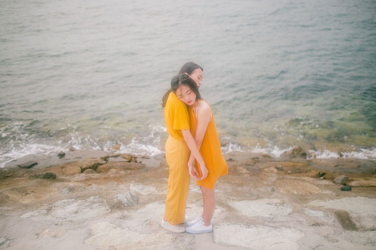 Two Girls Girls Yellow Intertwined Young Women Sea Wave Beach Water Beauty Sand Summer Women Standing Shore Horizon Over Water Coast Ocean Coastline Seascape Seaside Rocky Coastline