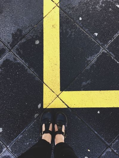 Low section of woman standing by yellow line on pavement