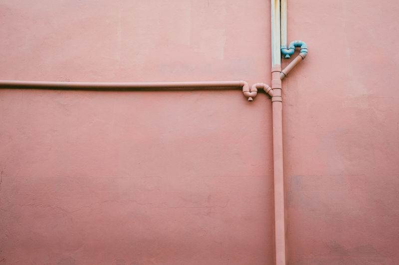 Water pipes on pink wall