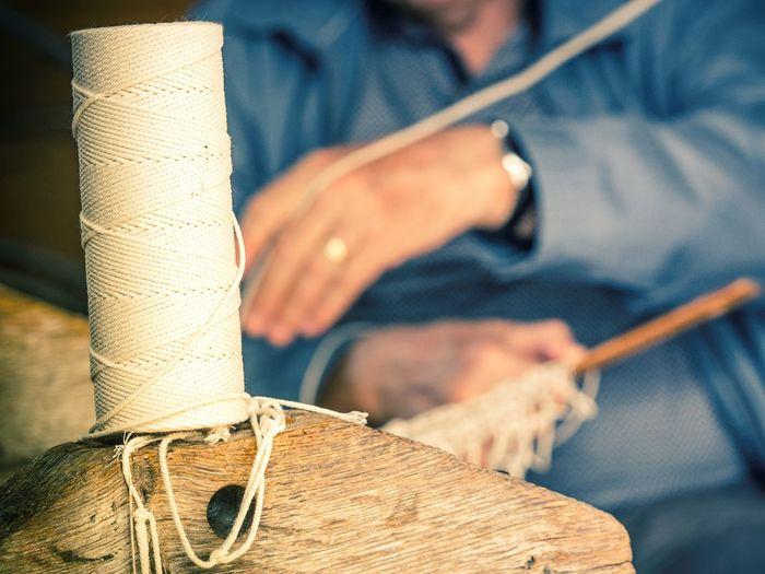 Close-up of thread spool on wood