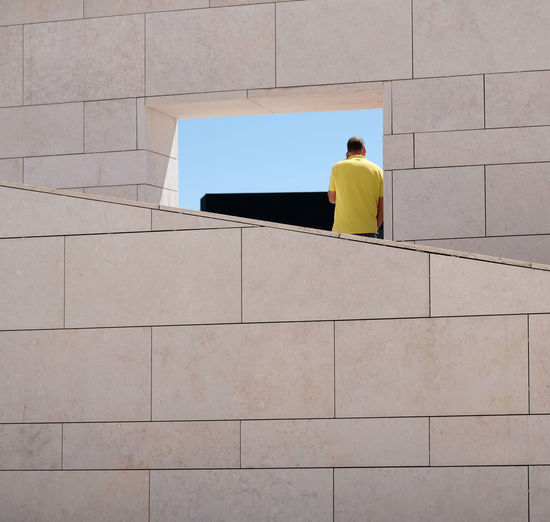 Rear view of man against wall