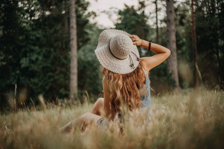 Rear view of woman wearing hat sitting on grassy field in forest