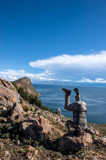 Man Doing Headstand On Top Of Rock Against Sea