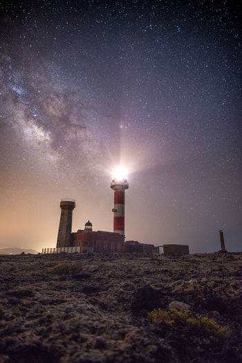 Lighthouse amidst buildings against sky at night