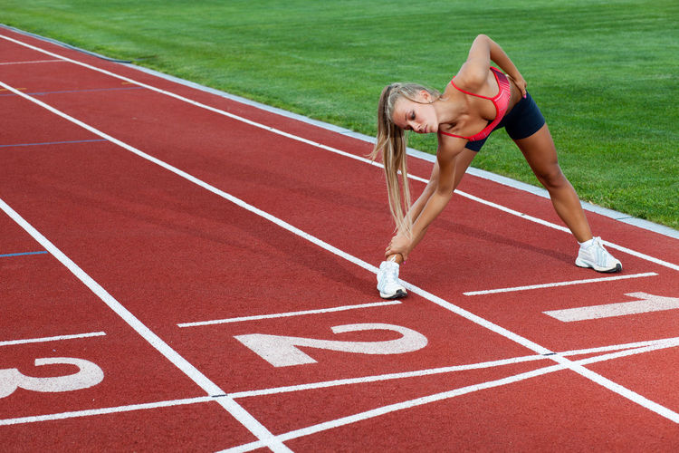 Sporty woman in a sports suit doing training exercises before running Sport Track And Field Running Track Exercising Competition Healthy Lifestyle Athlete Young Adult Lifestyles Track And Field Athlete Competitive Sport People Sports Clothing Adult Sports Track Sports Race Women Running Full Length Outdoors Effort