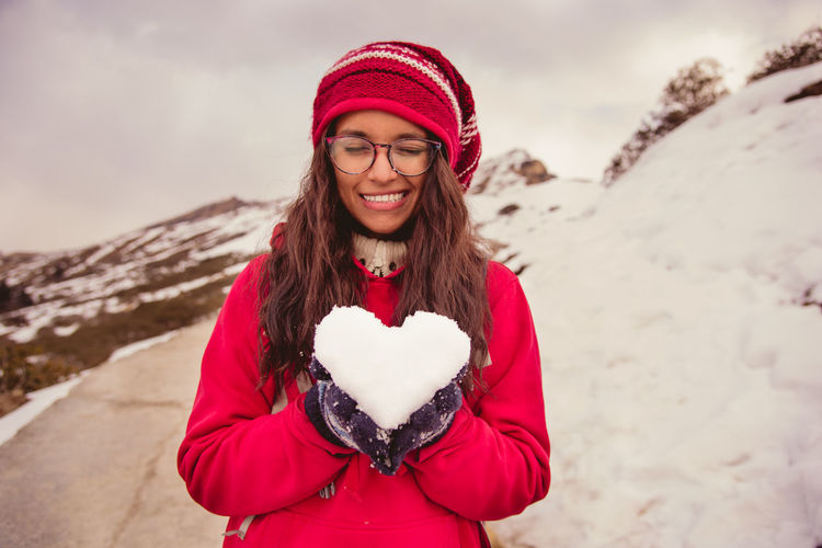 Portrait Of Smiling Young Woman Holding Snow On Mountain