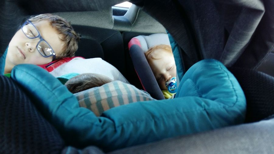 High Angle View Of Boys Sleeping In Car