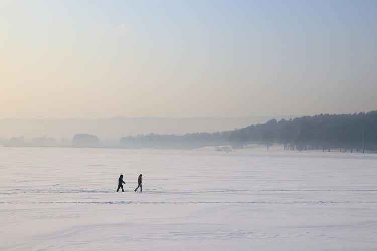 Walking through winter Cold Temperature Snow Winter Sky Two People Non-urban Scene Men Frozen Unrecognizable Person Environment Siberia Siberia, Russia Haze Winter Day