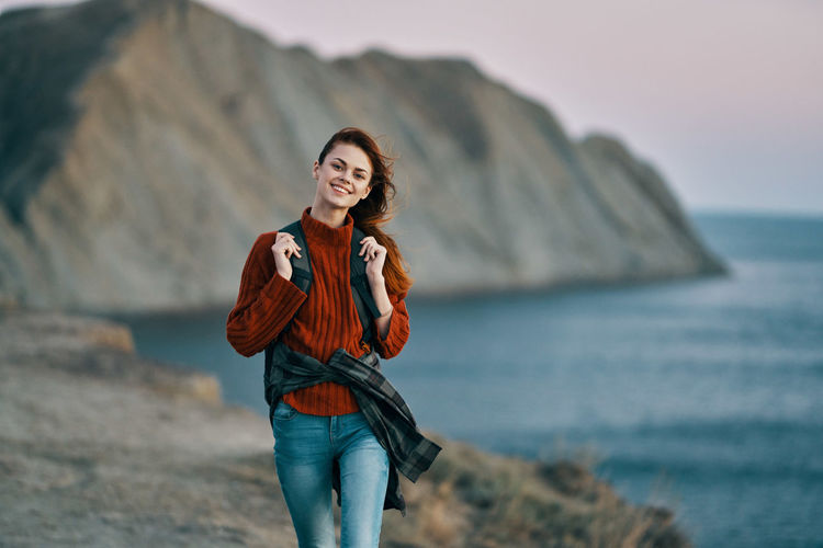 Portrait of smiling young woman standing on beach