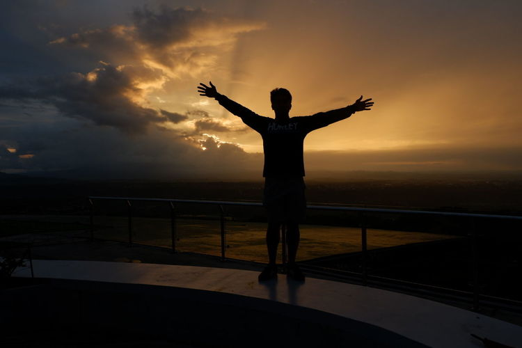 Rear View Of Silhouette Mid Adult Man With Arms Outstretched Standing Against Sky During Sunset