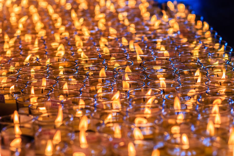 Full frame shot of illuminated candles in glasses at church