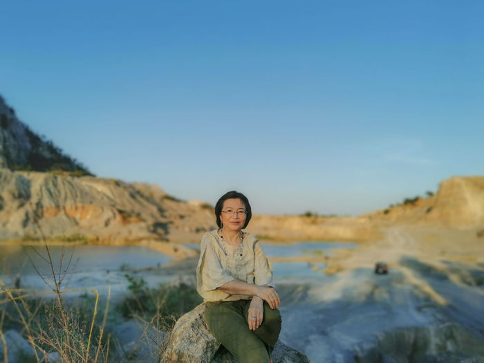 Portrait of smiling young woman sitting on rock against sky