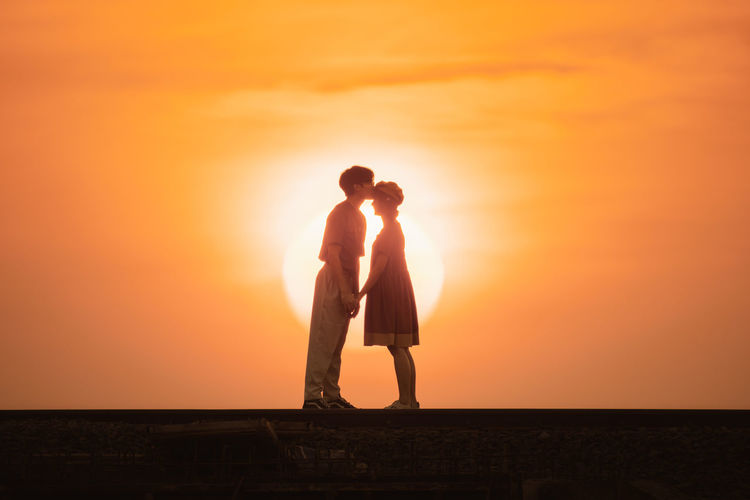 Couple standing against orange sky during sunset