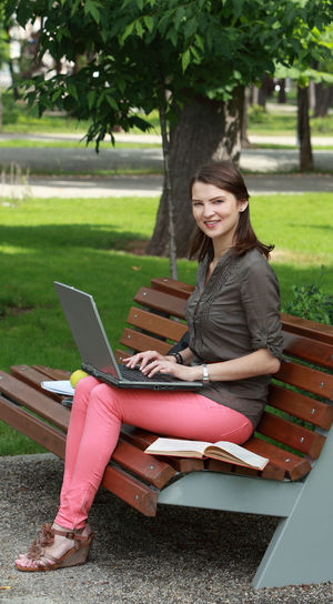 Young woman with a laptop sitting on a bench in an urban park. Laptop Sitting Using Laptop One Person Computer Wireless Technology Technology Communication Bench Connection Young Adult Smiling Adult Casual Clothing Outdoors Woman Young Woman Student Studying Device Screen Internet Park Urban Park