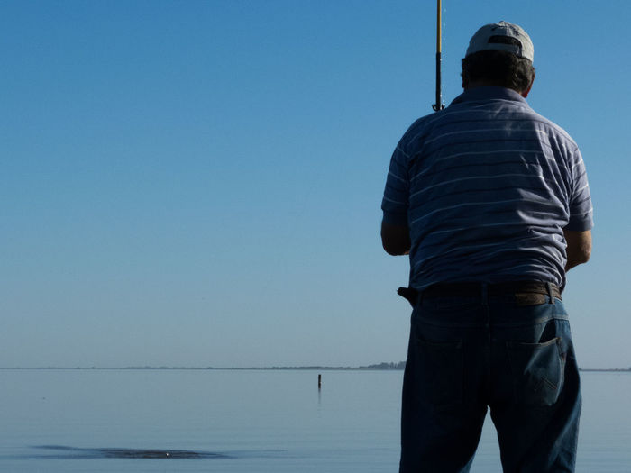 Rear view of man fishing in sea against clear blue sky