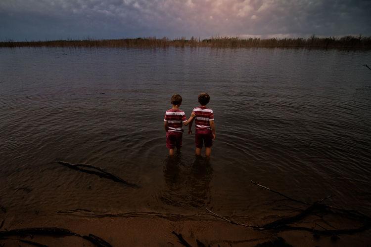 Rear view of men in lake against sky