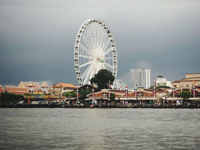 Ferris wheel by river against buildings in city