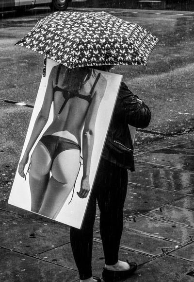 Bikini Weather? Advertising Black & White Rain Advert Advertisement Bikini Black And White Clothed  Day One Person Outdoors People Rainy Real People Sandwich Board Umbrella