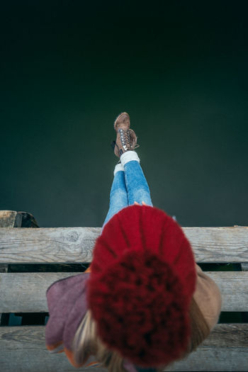 Directly above shot of woman sitting on pier over sea