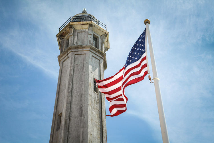 Patriotism Flag Sky Nature Low Angle View Architecture Built Structure Day Striped Cloud - Sky Building Exterior No People Tower Pole Outdoors Red Blue Wind Independence National Icon USA Lighthouse