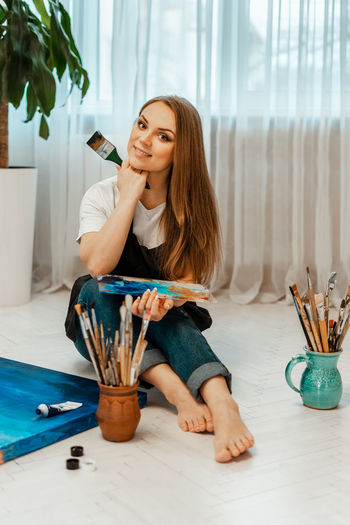 Portrait of woman holding with brushes and palette sitting on floor