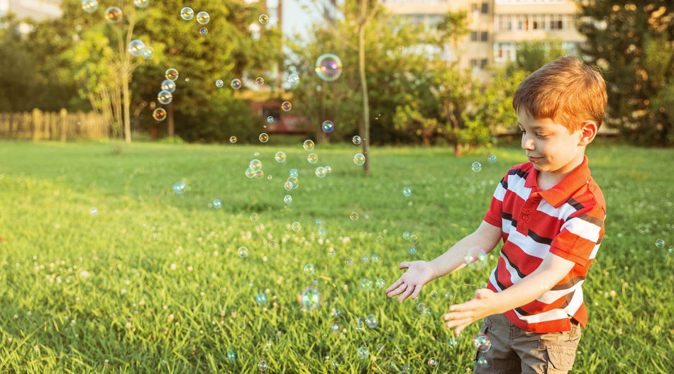 Smiling boy playing with bubbles while standing at park