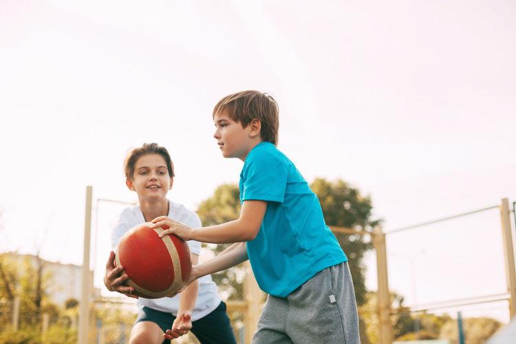 Boys playing basketball against clear sky