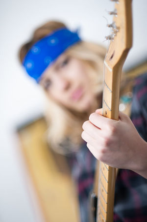 Young beautiful woman Blond Hair Chords Electric Guitar Female Guitar Neck Human Hand Indoors  Music Musical Instrument One Person People Playing Rocker Selective Focus Skill  Sound Stringed Instrument Woman Young Adult