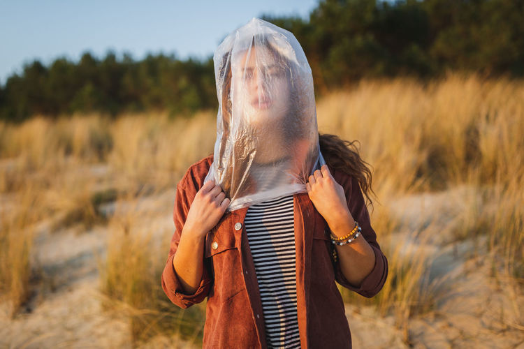 Young woman with face covered by plastic bag standing at beach