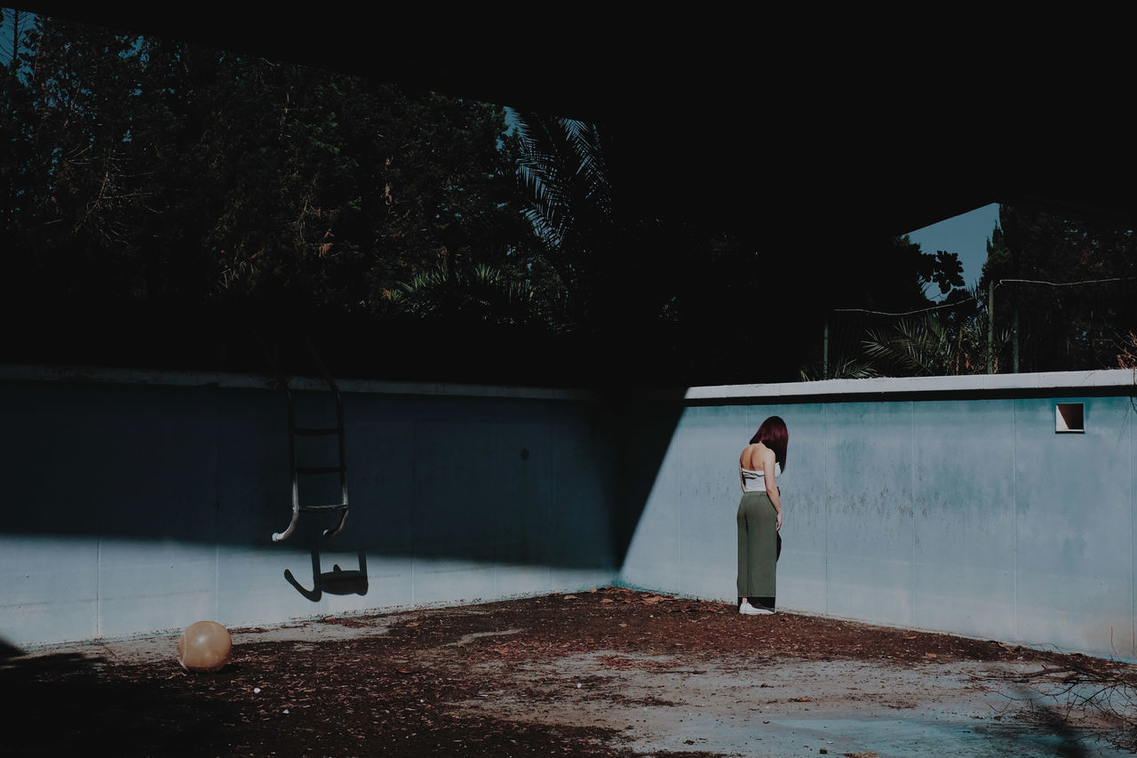 Full length of woman standing in abandoned swimming pool