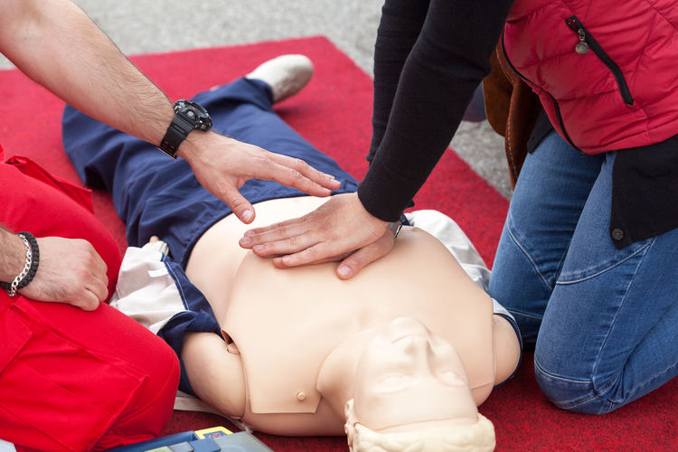 Midsection of paramedic practice with cpr dummy