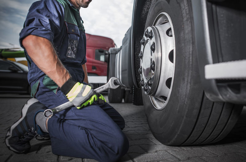 Low section of mechanic holding wrench sitting by tire outdoors