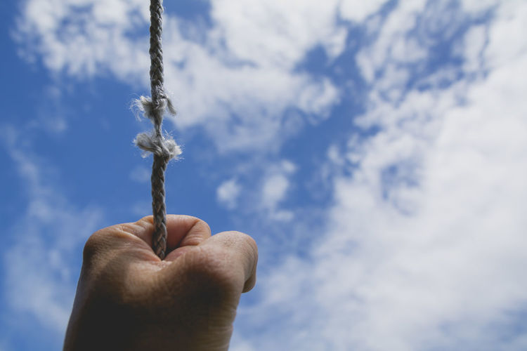 Cropped hand holding string against sky