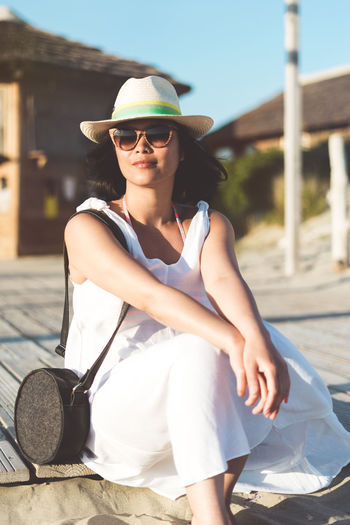 Young Woman Wearing Sunglasses Sitting On Boardwalk At Beach