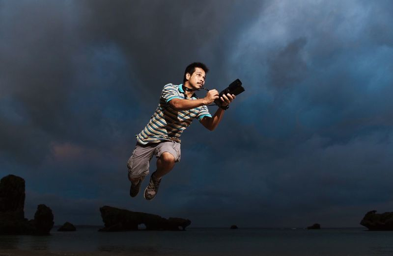 Man With Camera Levitating Over Sea Against Sky At Night