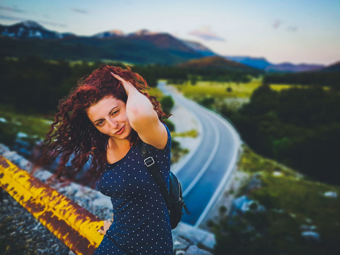 Portrait of smiling young woman standing on road