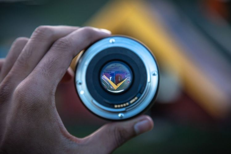Cropped image of person holding camera lens while looking at tent
