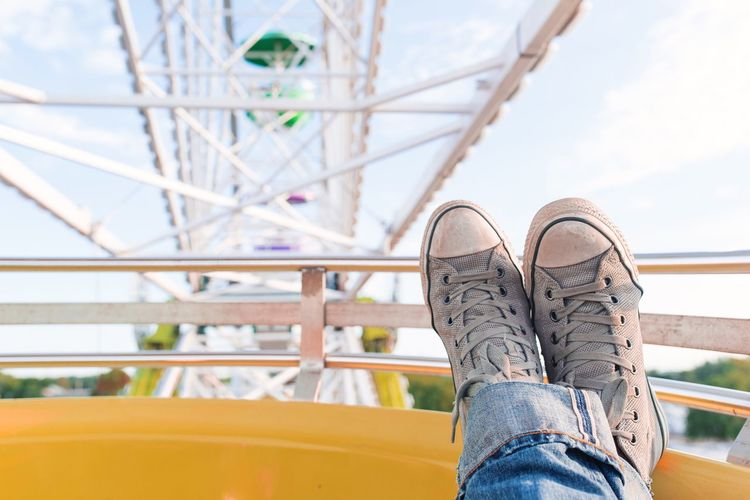 Low section of person wearing canvas shoe on ferris wheel