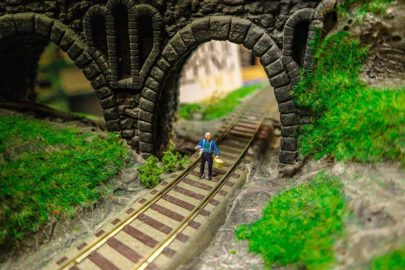 Man walking on arch bridge