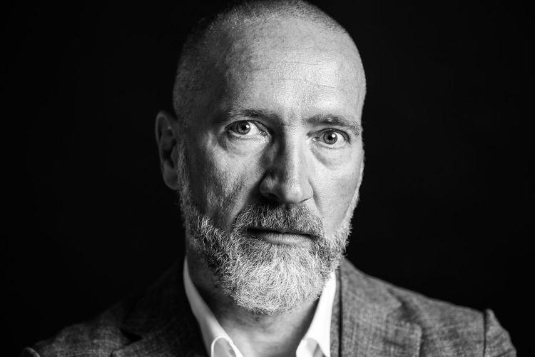 Close-up portrait of man on black background