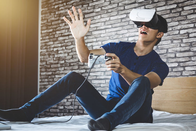 Young man looking through virtual reality simulator while sitting on bed at home