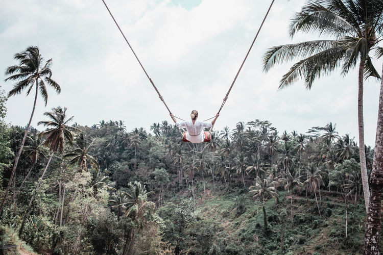 Woman sitting on swing by palm trees against sky