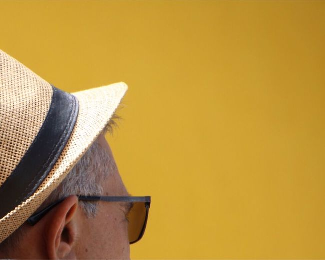 Close-up of man wearing hat against yellow background