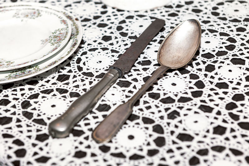 Tin spoon and knife on the table . ancient kitchen utensils . handmade embroidered tablecloth