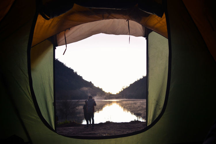 Friends standing by lake seen through tent