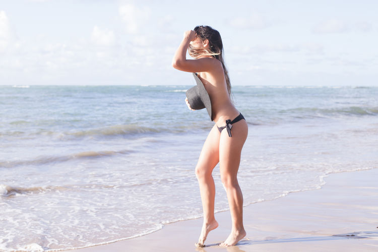 Sensuous young woman standing on sea shore