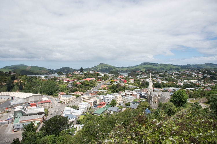 Port Chalmers, Dunedin, New Zealand-December 11,2016: Elevated view over the city landscape with green rolling hills in Port Chalmers, Dunedin, New Zealand Church Community Dunedin Road Rooftop Architecture City Greenery High Angle View Iona Landscape Mountain Nature Neighborhood New Zealand Port Chalmers Residential District Scenery Sky Street Tower Town TOWNSCAPE Tree Village