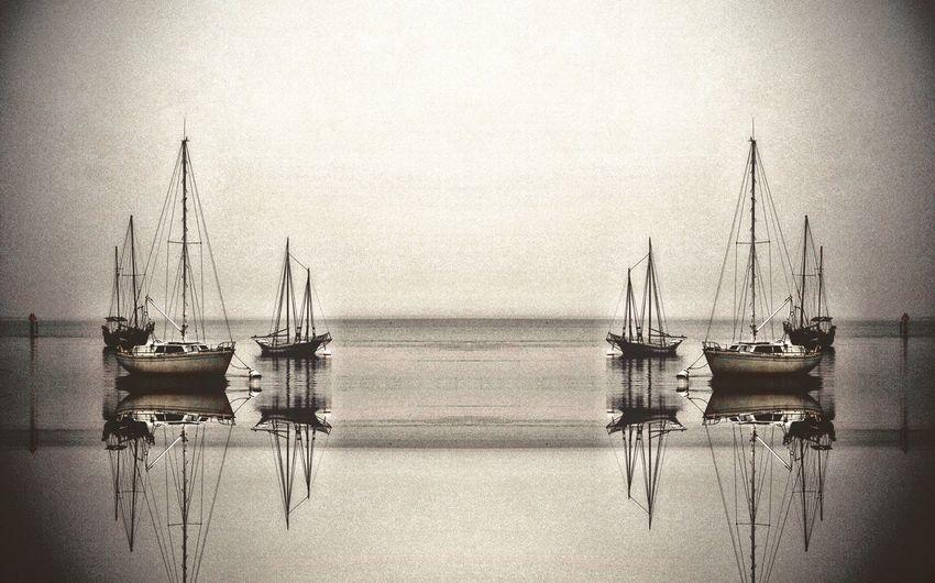 Sailboats moored in sea
